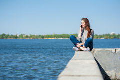 女孩坐栏杆01 免版税库存照片