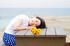 女孩坐桌用雏菊向日葵 免版税库存照片