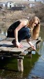 女孩坐桥梁 库存照片