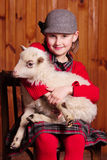 女孩坐椅子,举行在他的胳膊的一只在图片的羊羔和神色 在农场 免版税库存图片
