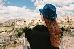 女孩坐椅子,放松并且敬佩卡帕多细亚小山的一个惊人的看法在土耳其 放松,休息 图库摄影