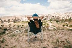 女孩坐椅子,放松并且敬佩卡帕多细亚小山的一个惊人的看法在土耳其 放松,休息 免版税库存图片