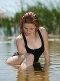 女孩坐水年轻人 库存照片