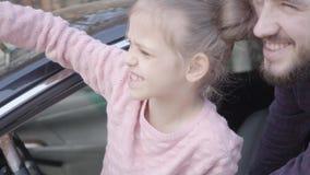 女孩坐汽车关闭的驾驶席  在汽车的微笑的有胡子的人身分在他的女儿附近 股票视频