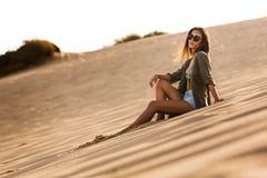 女孩坐沙丘 库存照片