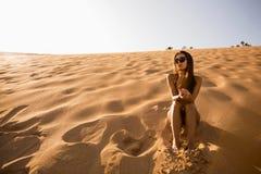 女孩坐沙丘 库存图片