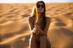 女孩坐沙丘 免版税图库摄影
