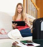女孩坐沙发在行李附近 免版税库存图片
