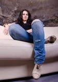 女孩坐沙发 免版税图库摄影