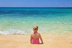 女孩坐沙子海滩 库存图片