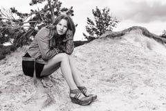 女孩坐沙子 bw 库存照片