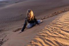 女孩坐沙漠沙丘 库存图片