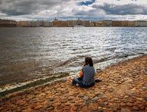 女孩坐河岸在彼得斯堡 图库摄影