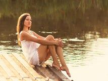 女孩坐河岸 库存照片