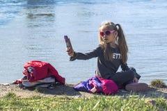 女孩坐河的河岸有电话的 在一个温暖的春日 女孩做一selfie 免版税库存图片