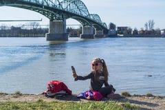 女孩坐河的河岸有电话的 在一个温暖的春日 女孩做一selfie 库存图片