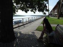 女孩坐河的河岸 库存照片