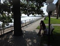 女孩坐河的河岸 图库摄影