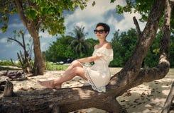 女孩坐注册海滩 马尔代夫 海岛的基于 免版税库存照片