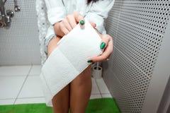 女孩坐洗手间拿着手纸 问题,肚腑,个人卫生的概念椅子的, 库存图片