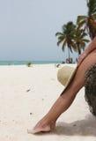女孩坐海滩结构树 免版税库存图片