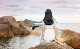 女孩坐海边岩石 库存图片
