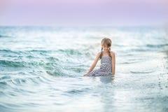 女孩坐海滩 免版税库存图片
