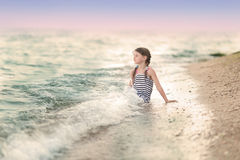 女孩坐海滩 免版税库存照片