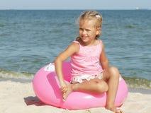 女孩坐游泳的一个圈子在海附近 库存图片
