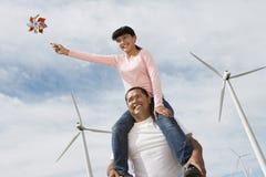 女孩坐父亲的肩膀在风力场 库存图片