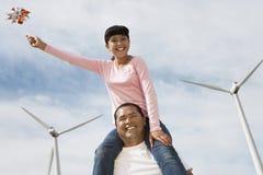 女孩坐父亲的肩膀在风力场 免版税库存图片