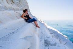 女孩坐白色峭壁叫的倾斜& x22; 斯卡拉dei Turchi& x22;在西西里岛 免版税库存图片