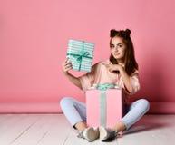女孩坐的地板生日礼物 免版税库存照片
