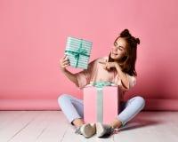 女孩坐的地板生日礼物 库存图片