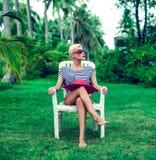 女孩坐的基于一把椅子在公园 免版税图库摄影