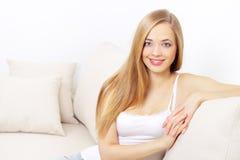 女孩坐的微笑的沙发 库存照片