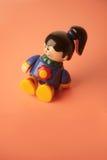 女孩坐的微笑的玩具 库存图片