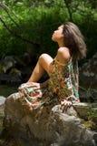 女孩坐的石头 免版税库存照片