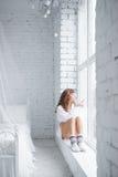 女孩坐的窗台 顶视图 免版税库存图片