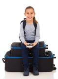 女孩坐的行李袋子 库存照片