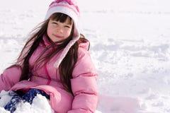 女孩坐的雪年轻人 免版税库存照片