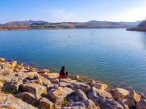 女孩坐看有天鹅游泳的她湖 免版税库存照片