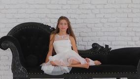 女孩坐看照相机的一个黑沙发 股票录像