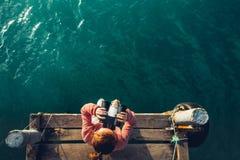女孩坐码头并且看海通过双筒望远镜,顶视图 冒险假期发现旅行概念 库存图片