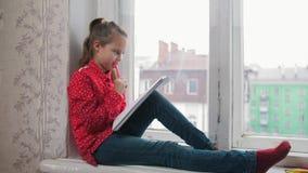 女孩坐窗口基石和画,微笑在城市的backround 免版税库存图片