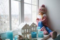 女孩坐窗口基石 免版税库存图片