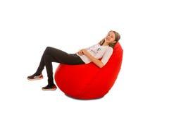 女孩坐红色装豆子小布袋椅子 免版税库存图片