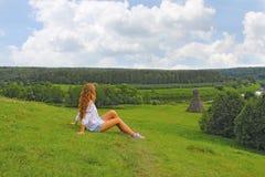 女孩坐绿草在夏天 免版税图库摄影