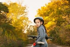 女孩坐自行车 步行在秋天 乘坐在路 免版税库存图片