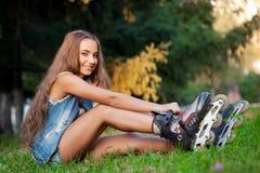 女孩坐草和投入冰鞋 库存图片